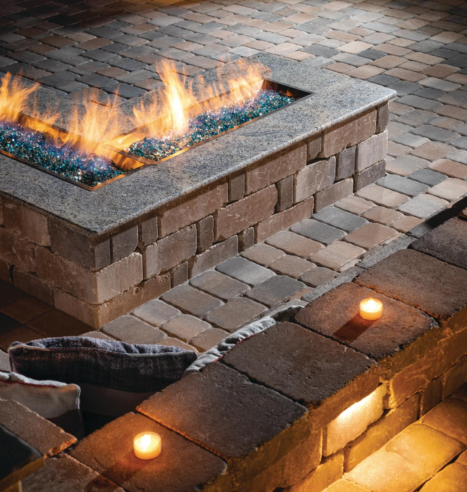 built-in L-shaped cobbled paver patio with custom fire table